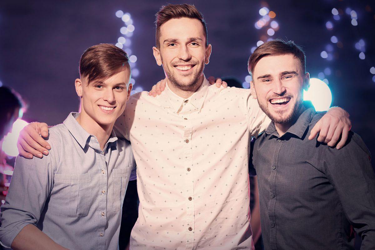 Drei junge Männer bei einer Party, der mittlere hat die Arme um die beiden anderen gelegt.